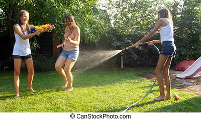 4k video of happy family playing with watering garden hose and water toy guns on grass at backyard on hot sunny day