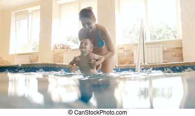 4k video of happy laughing young mother with cheerful toddler boy walking down the stairs in indoor swimming pool