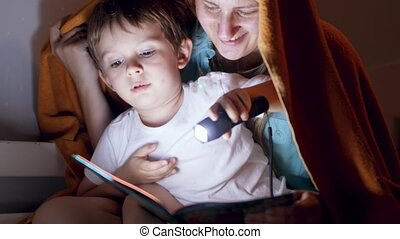 4k footage of happy smiling mother with little son sitting under blanket at night and reading book with flashlight