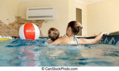 4k video of happy smiling toddler boy swimming with mother...