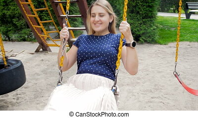 4K video of happy smiling woman having fun on swing in park...