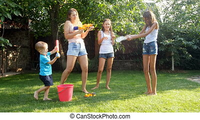 4k video of happy young family having water guns battle at...