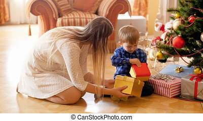 4k video of happy young mother sitting with her little son under Christmas tree and opening Christmas gifts and presents. Family giving and receiving presents on winter holidays and celebrations.