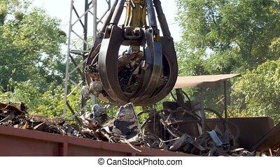 4k video of hydraulic claw manipulator carrrying old metal ...