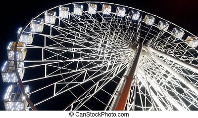 4k video of illuminated big ferris wheel in amusement park at night