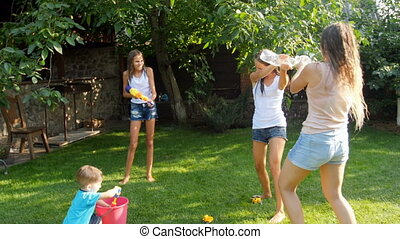 4k video of laughing happy family having water battle on grass at backyard.