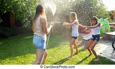 4k video of laughing happy family playing with garden hose and water guns at house backyard