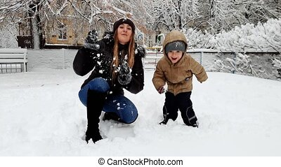 4k video of laughing toddler boy playing with young mother on playgrund covered with snow. Family throwing snowballs
