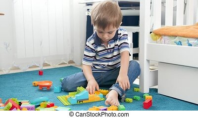 4k video of little 4 years old boy playing with toys on ...