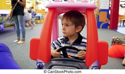 4k video of little 4 years old boy riding in pedal car on ...
