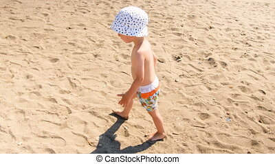4k video of little barefoot toddler boy feeling hot sand on sea beach at sunny day
