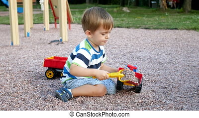 4k video of little boy playing with toys on playground...