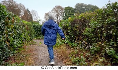 4k footage of little boy running away from camera in the labyrinth made of beautiful bushes in park