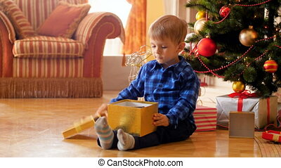 4k video of little cute boy sitting on the floor next to Christmas tree and opening box with present from Santa Claus. Family having good time and fun on winter holidays and celebrations.