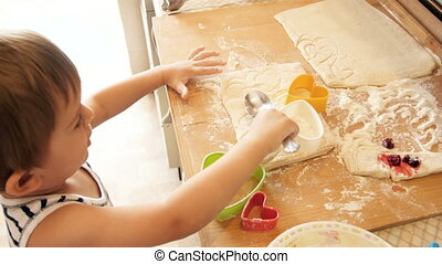 4k video of little funny boy playing with dough and ingredients on kitchen