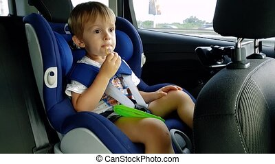 4k video of little toddler boy eating while riding in car....
