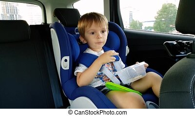 4k video of little toddler boy eating while riding in car. Child sitting in safety car seat and eating cookie