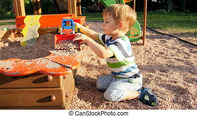 4k video of little toddler boy loading gravel in toy loader...