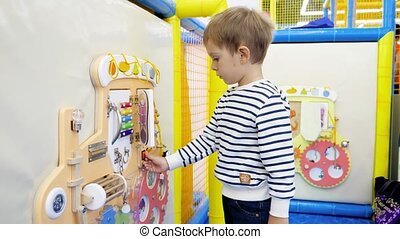 4k video of little toddler boy playing with busy board on playground. Elementary education and motility for children