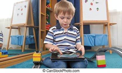 4k video of little toddler boy sitting on carpet at hid ...