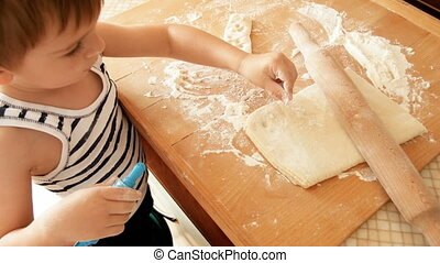 4k video of little toddler boy sprnkling dough with flour on wooden kitchen countertop