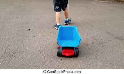 4k video of little toddler boy walking and pulling toy truck...