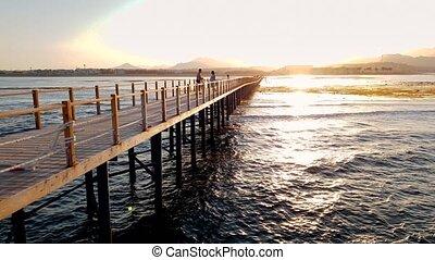 4k video of long wooden pier in the ocean. Sea waves rolling...