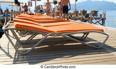 4k video of people relaxing on sunbeds on wooden pier at sunny day on sea beach