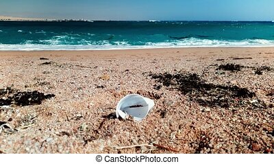 4k video of plastic cup, gardbage and debris lying on th...