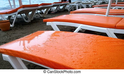 4k video of rain drops falling on empty sunbeds at sea beach