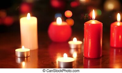 4k video of red and white burning candles against glowing colorful lights at night. Perfect background or backdrop for Christmas or New Year