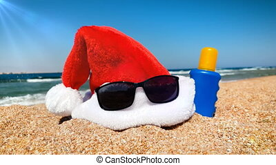 4k video of Santa hat, sunglasses and sunscreen lotion lying...