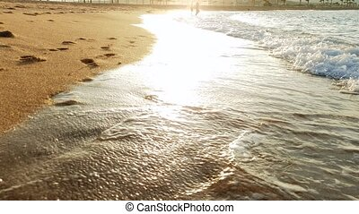 4k video of sea waves rolling over footprints on wet sand on...