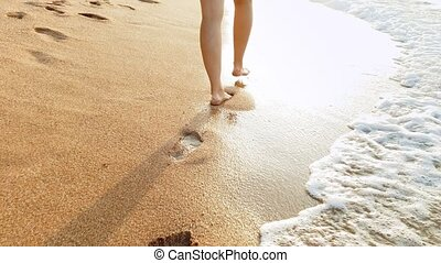 4k video of sexy female feet walking on wet sand and sea...