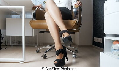 4k video of sexy young owman with long legs posing in big boss office chair