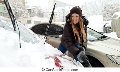 4k video of smiling female driver removing snow from her car...