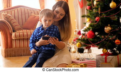 4k video of smiling young mother with her little boy watching cartoons on mobile phone under Christmas tree
