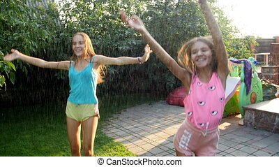 4k video of two happy laughing teenage girls dancing under water spraying from garden water hose