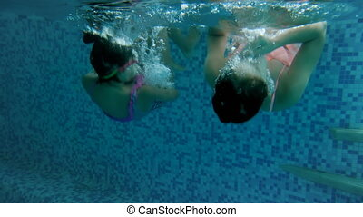 4k video of two teenage girls in goggles learning diving under water at swimming pool