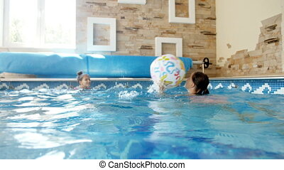 4k video of two teenage girls playing with colorful beach ball in the indoor swimming pool