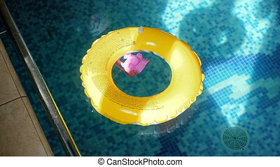 4k video of yellow inflatable ring and plastic toy on water...