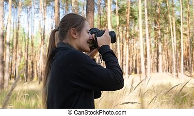 4k video of young female wildlife photographer making images...