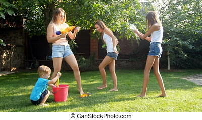 4k video of young mother having water guns battle with her...