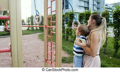 4k video of young mother lifting her toddler son and helping him hanging on rings at park playground