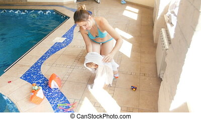 4k video of young mother wiping with towel her wet toddler...