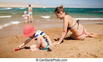 4k video of young mother with her child son playing with toy car on the sea beach. Family relaxing during summer beach vacation