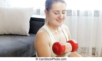 4k video of young smiling woman in sports clothes exercising with dumbbells