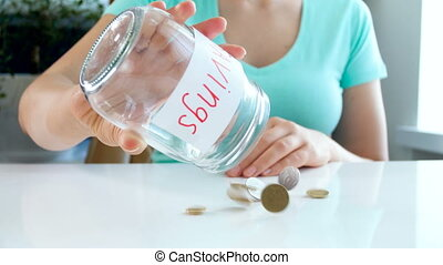 4k video of young woman has few coins in glass jar for...