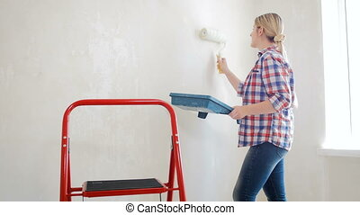 4k video of young woman holding palette and painting walls...