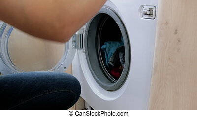 4k video of young woman in jeans taking out wet clean clothes from washing maching after laundry has finished